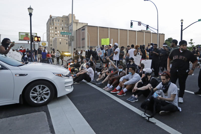Protesters sit at an intersection during a protest over the deaths of George Floyd and Breonna Taylor, Saturday, May 30, 2020, in Louisville, Ky. Breonna Taylor, a black woman, was fatally shot by police in her home in March. (AP Photo/Darron Cummings)