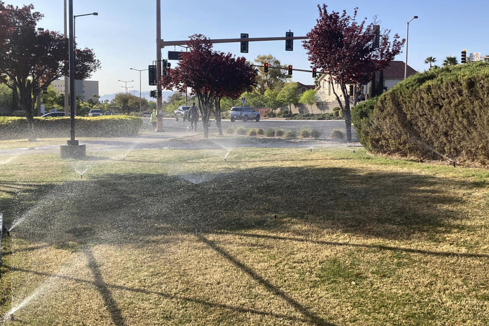 FILE - In this April 9, 2021, file photo, sprinklers water grass near a street corner in the Summerlin neighborhood of northwest Las Vegas. Nevada Gov. Steve Sisolak signed legislation on Friday, June 4 to make the state the first in the nation to ban certain kinds of grass. The measure will ban water users in southern Nevada from planting decorative grass in an effort to conserve water. (AP Photo/Ken Ritter, File)