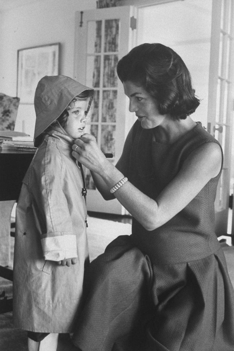 <p>Jackie makes sure her daughter, Caroline, is dressed appropriately for a rainy day in 1960. The mother and daughter were at their family home in Washington, D.C., before relocating to the White House.</p>