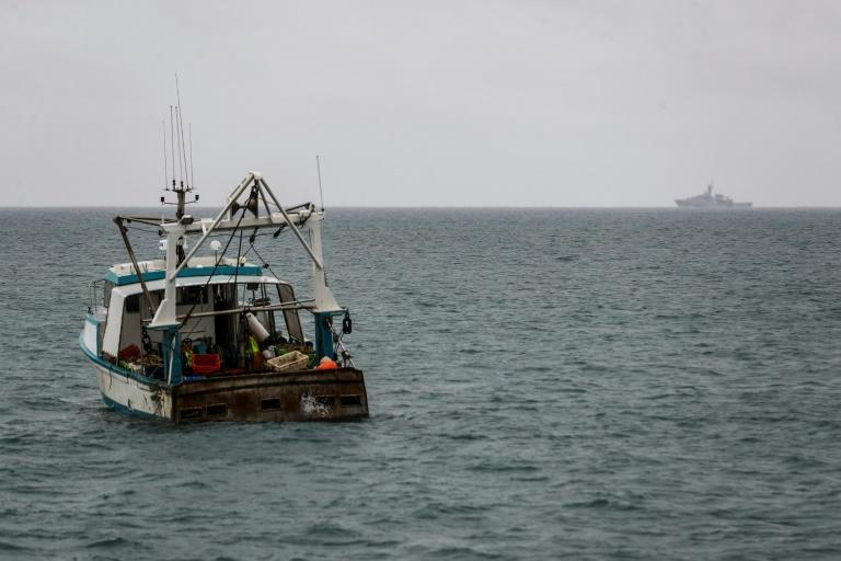 British naval ship the HMS Tamar, right, is watched by a fishing boat off the island of Jersey