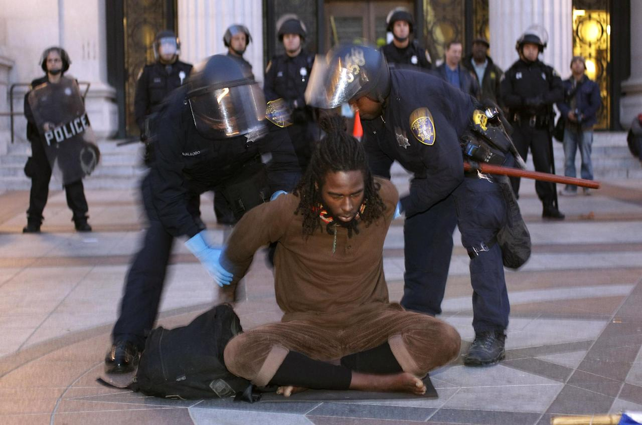 Police hold a demonstrator at an encampment for the Occupy Wall Street movement in Oakland, Calif., Monday, Nov. 14, 2011. Police in Oakland began clearing out a weeks-old encampment early Monday after issuing several warnings to Occupy demonstrators. (AP Photo/Paul Sakuma)