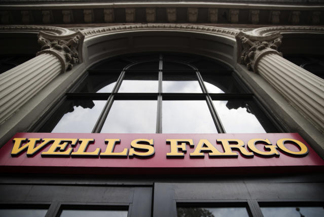 FILE – This Friday, Aug. 11, 2017, file photo shows a sign at a Wells Fargo bank location in Philadelphia. Wells Fargo stands to benefit from the new tax overhaul. (AP Photo/Matt Rourke, File)