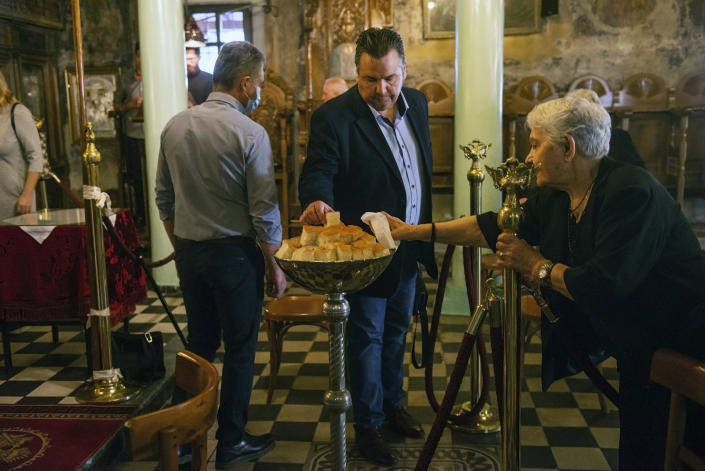 ADDS THAT THEY ARE TAKING BLESSED BREAD AFTER HOLY COMMUNION - In this Sunday, May 24, 2020, photo, a man and an elderly woman take a piece of bread that has been blessed, after receiving Holy Communion in a Greek Orthodox church in the northern city of Thessaloniki, Greece. Priests at the church use a traditional spoon to distribute Holy Communion. Contrary to science, the Greek Orthodox Church says it is impossible for any disease, including the coronavirus, to be transmitted through Holy Communion. (AP Photo/Giannis Papanikos)