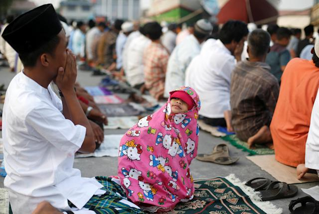 <p>A child looks at her father during prayers for the Muslim holiday of Eid Al-Adha at Sunda Kelapa port in Jakarta, Indonesia, Sept. 1, 2017. (Photo: Beawiharta/Reuters) </p>