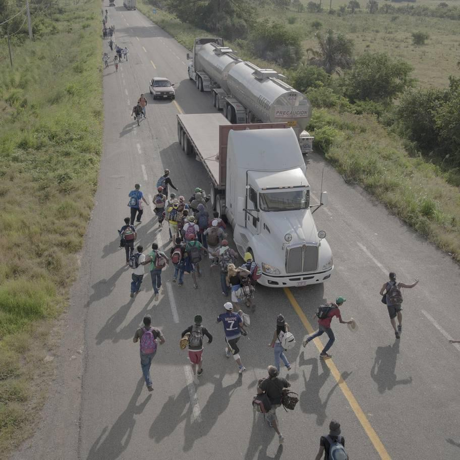 <p>People run to a truck that has stopped to give them a ride, outside Tapanatepec, Mexico, on 30 October 2018. Some drivers charged to give travelers a lift for part of the way, but most offered services free as a sign of support. (Pieter Ten Hoopen) </p>