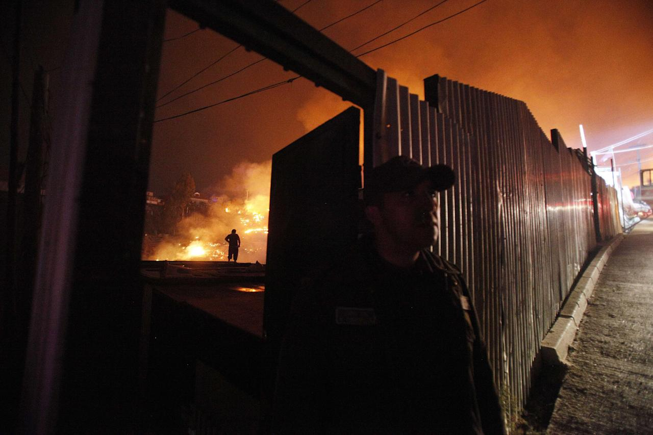 A man stands behind a wall as an out of control forest fire destroys homes in the city of Valparaiso, Chile, Sunday April 13, 2014. Firefighters struggled for a second night to contain blazes that reached this port city, killing at least a dozen people, destroyed hundreds homes and has forced the evacuation of thousands. (AP Photo/Luis Hidalgo)