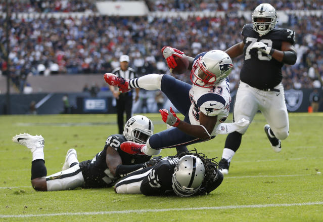 <p>New England Patriots Dion Lewis, center, scores a touchdown against Oakland Raiders Karl Joseph, bottom left, and Reggie Nelson, bottom right, during the first half of their 2017 NFL Mexico Game at the Estadio Azteca in Mexico City, Nov. 19, 2017. (Photo by Jessica Rinaldi/The Boston Globe via Getty Images) </p>
