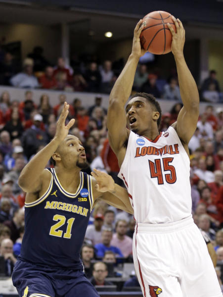 Louisville guard Donovan Mitchell (45) shoots over Michigan guard Zak Irvin (21) during the first half of a second-round game in the men's NCAA college basketball tournament in Indianapolis, Sunday, March 19, 2017. (AP Photo/Michael Conroy)