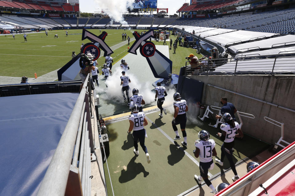 Tennessee Titans players take the field with no fans in the stadium for an NFL football game against the Jacksonville Jaguars Sunday, Sept. 20, 2020, in Nashville, Tenn. (AP Photo/Wade Payne)
