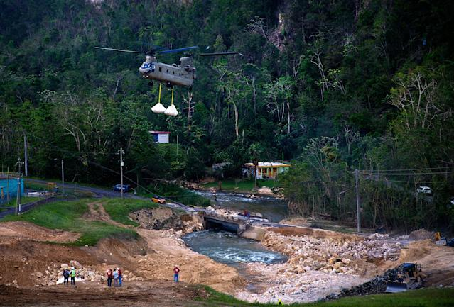 <p>A U.S. Army helicopter transports material to repair the Guajataca Dam, damaged during Hurricane Maria, in Quebradillas, Puerto Rico, Tuesday, Oct. 17, 2017. The dam was built around 1928, and holds back a man-made lake. (Photo: Ramon Espinosa/AP) </p>