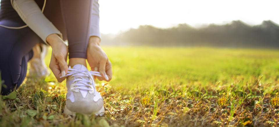 young woman runner tying her shoes preparing for a jog outside at morning