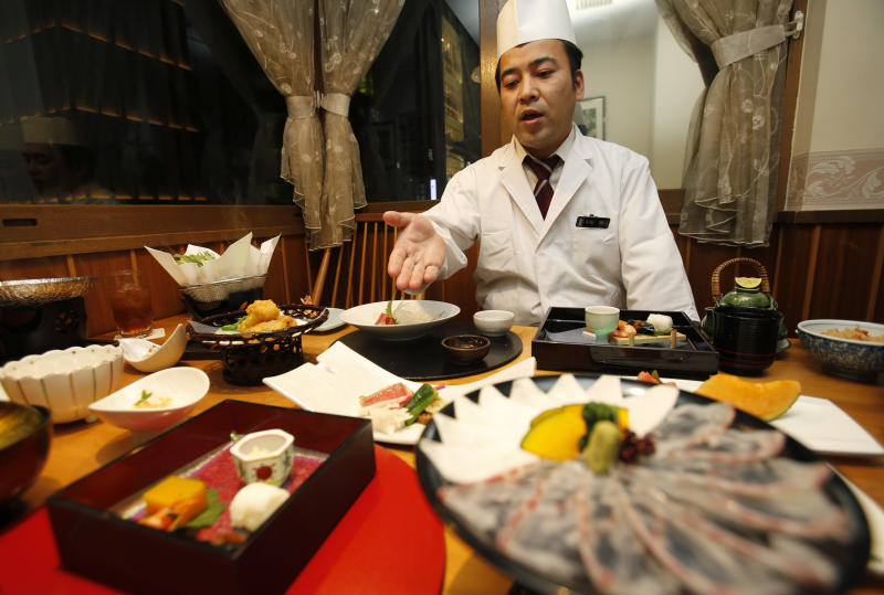 """In this Wednesday, Nov. 27, 2013 photo, chief chef Kenji Uda explains about the menu at Japanese restaurant Irimoya Bettei in Tokyo. Washoku, the traditional cuisine of Japan, is being considered for designation as part of the world's priceless cultural heritage by the U.N. this week. But even as sushi and sake booms worldwide, purists say its finer points are candidates for the endangered list at home. The younger generation is increasingly eating Krispy Kreme donuts and McDonald's, not rice. Uda, 47, says he was 17 when he decided to devote his life to washoku. """"Japanese food is so beautiful to look at,"""" he said. """"But it takes a lot of time. People are working and busy, and no longer have that kind of time."""" (AP Photo/Shizuo Kambayashi)"""
