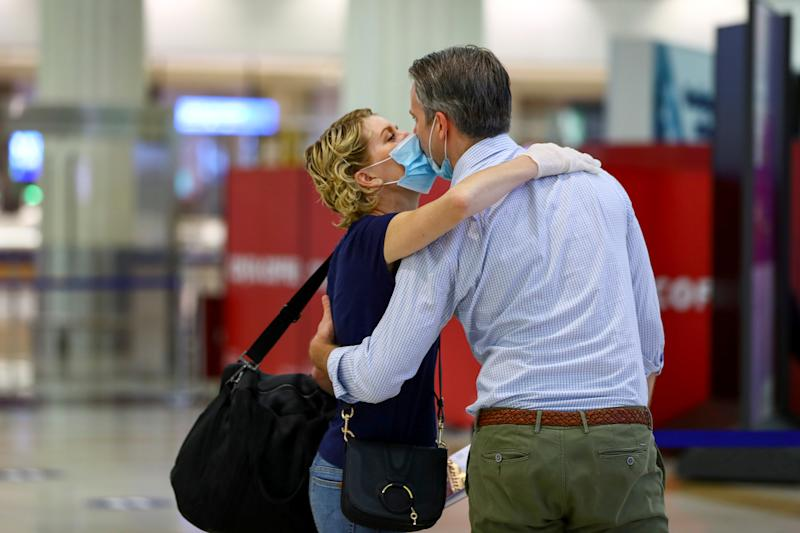 A man wearing a protective mask kisses his wife before she boards at Dubai International Airport, as Emirates airline resumed limited outbound passenger flights amid the outbreak of the coronavirus disease (COVID-19) in Dubai, UAE April 27, 2020. REUTERS/Ahmed Jadallah TPX IMAGES OF THE DAY