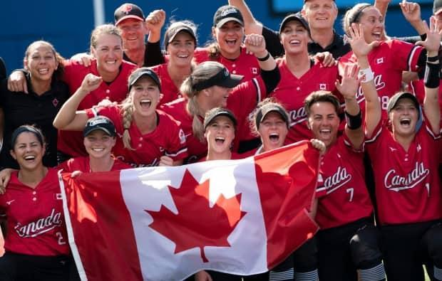 Canada's women's softball team poses for a photo with the Canadian flag after their win on Tuesday over Mexico in the bronze medal game at the Tokyo Olympics. (Adrian Wyld/The Canadian Press - image credit)