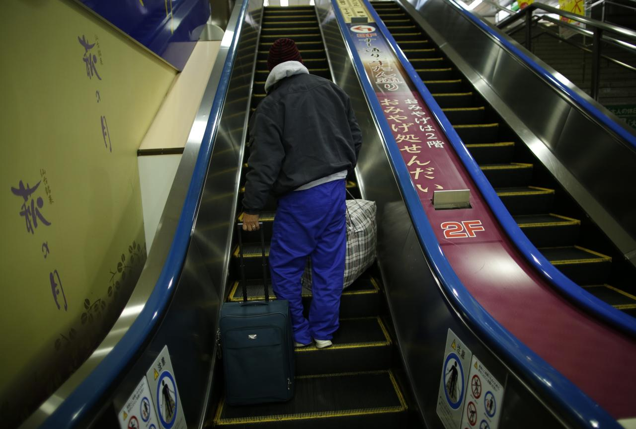 Shizuya Nishiyama, a 57-year-old homeless man from Hokkaido, takes an escalator at Sendai Station in Sendai, northern Japan December 18, 2013. Picture taken December 18, 2013. To match Special Report FUKUSHIMA-WORKERS/ REUTERS/Issei Kato (JAPAN - Tags: CRIME LAW DISASTER BUSINESS EMPLOYMENT CONSTRUCTION POLITICS)