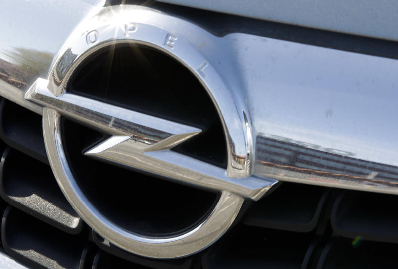 "FILE - In this March 26, 2012 file picture a car shows the Opel logo while reflecting the front of the Opel car manufacturer plant in Bochum on,  in Bochum, Germany.  General Motors says its Opel subsidiary is in ""active talks"" about using its German factories more efficiently.   Proposals up for discussion between the company's management, trade unions and works councils include putting off a wage increase slated for this year and no layoffs before 2016 instead of through 2014.  GM has been struggling to return its European business to profitability amid tough competition among mass-market carmakers.  The U.S. carmaker could also build non-Opel models at its German plants in order to better use its plant capacity.   But the Bochum plant will not get further production orders after the current Zafira Tourer comes to the end of its life cycle. (AP Photo/Frank Augstein,file)"