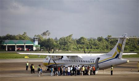 People form a line to board a plane in Yangon airport