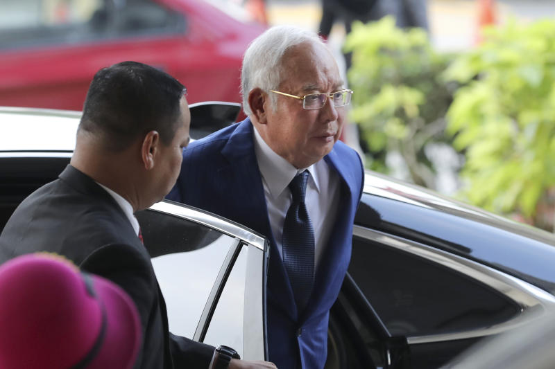 Former Malaysian Prime Minister Najib Razak, right, arrives at Kuala Lumpur High Court in Kuala Lumpur, Malaysia, Tuesday, Aug. 27, 2019. Malaysian prosecutors have wrapped up their case against Najib in his first corruption trial. Najib faces 42 charges of corruption, abuse of power and money laundering in five criminal cases linked to the multibillion-dollar looting of the 1MDB state investment fund. His second trial is due to begin Wednesday but could be delayed. Najib denies wrongdoing and accuses the new government of seeking political vengeance. (AP Photo/Vincent Thian)