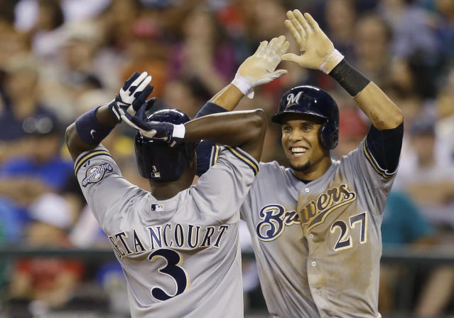 Milwaukee Brewers' Carlos Gomez (27) greets Yuniesky Betancourt (3) at the plate after Betancourt hit a grand slam against the Seattle Mariners in the fifth inning of a baseball game, Friday, Aug. 9, 2013, in Seattle. (AP Photo/Ted S. Warren)