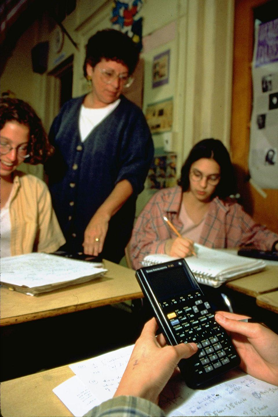 <p>An advanced placement student works out a math problem using his Texas Instruments graphing calculator. </p>