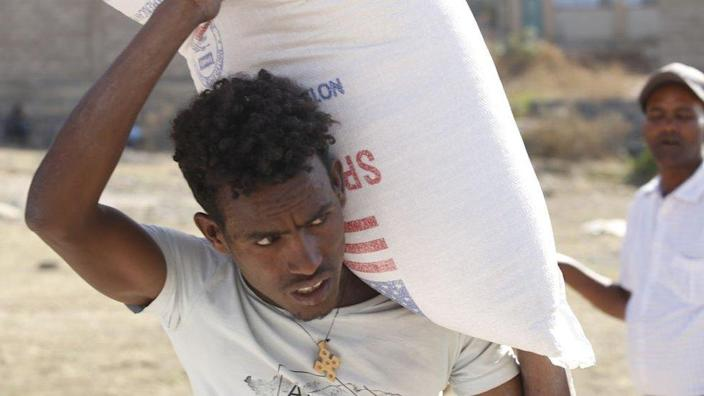 Tigray people, fled due to conflicts and taking shelter in Mekelle city of the Tigray region, in northern Ethiopia, receive the food aid distributed by United States Agency for International Development (USAID) on March 8, 202