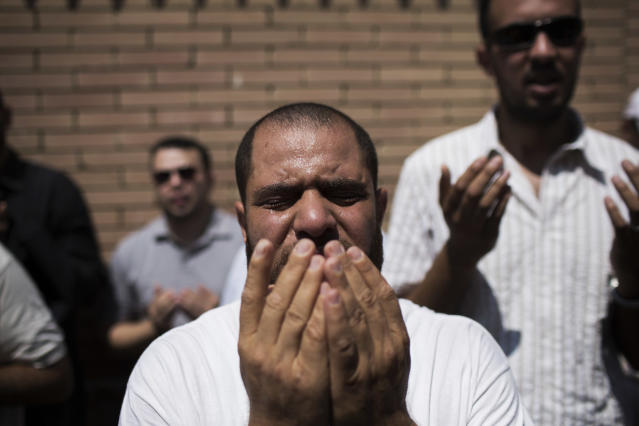 A friend of Ammar Badie, the son of Muslim Brotherhood's spiritual leader Mohammed Badie, who was killed Friday by Egyptian security forces during clashes in Ramses Square, cries while attending his burial in Cairo's Katameya district, Egypt, Sunday, Aug. 18, 2013. Egyptian authorities raided homes of Muslim Brotherhood members Sunday in an apparent attempt to disrupt the group ahead of mass rallies by supporters of the country's ousted president. (AP Photo/Manu Brabo)