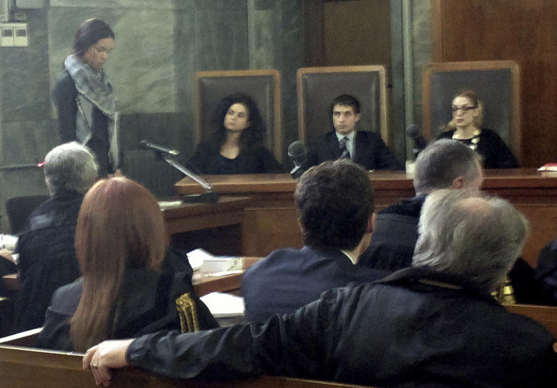 "Karima el-Mahroug, from Morocco, the woman at the center of a sex scandal involving former Italian Premier Silvio Berlusconi, is seen in the witness stand at left as she testifies for the first time in the trial of three Berlusconi aides charged with recruiting her and other women for prostitution, in Milan's courthouse, Italy, Friday, May 17, 2013. El-Mahroug, known by the nickname Ruby Heart Stealer, has made carefully orchestrated statements to the media since the scandal broke but has never publicly given sworn testimony. Both she and Berlusconi deny having had sex. Prosecutors in Berlusconi's separate trial on charges of paying for sex with a minor and trying to cover it up say her testimony is unreliable and are relying on her sworn statements. Writing above judges reads in Italian ""The law is equal for all.""(AP Photo/Luca Bruno)"