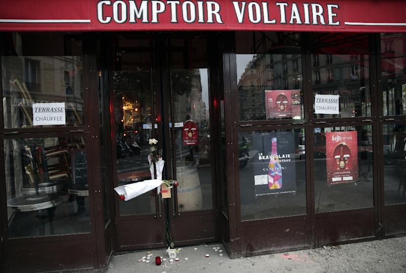 Flowers are placed on the doors of the Comptoir Voltaire cafe at the site of an attack on November 15, 2015 in Paris, after a series of gun attacks occurred across the city (AFP Photo/Kenzo Tribouillard)