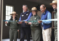 In this Friday, Oct. 1, 2021, photo, from left: Yenyen Chan, Yosemite Park Ranger, Frank Dean, President of Yosemite Conservancy, Cicely Muldoon, Superintendent of Yosemite National Park, Jack She, Yosemite Park advocate, and Adam Ramsey, Supervisory Yosemite Park Ranger, cut the ribbon at the dedication ceremony of the restored 1917 Chinese Laundry building at Wawona in Yosemite National Park, Calif. Officials unveiled on Friday a new sign and exhibit inside a building originally used as a laundry by Chinese workers at Yosemite's Wawona Hotel, formally recognizing Chinese Americans' contributions to the national park's history. (John Walker/The Fresno Bee via AP)