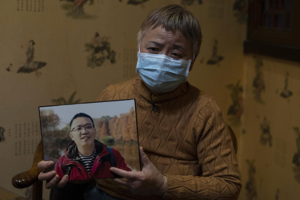 """Zhong Hanneng holds a photo of her son, Peng Yi, and talks about his difficulties in getting tested for COVID-19, eventually dying from the disease, in Wuhan in central China's Hubei province on Saturday, Oct. 17, 2020. """"There were very, very few tests, basically none. ... if you couldn't prove you were positive, you couldn't get admitted to a hospital. ... The doctor said there was nothing that could be done."""" (AP Photo/Ng Han Guan)"""