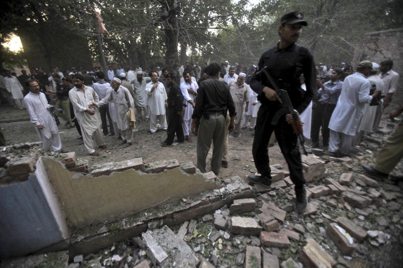 Pakistani policemen and civilians stand at the site of an explosion in a Sunni shrine in Peshawar, Pakistan, Thursday, June 21, 2012. A Pakistani police officer said that two children have been killed by an explosion at a Sunni shrine in Peshawar as dozens of people gathered there. (AP Photo/Mohammad Sajjad)