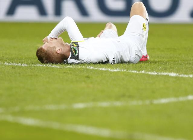 Borussia Dortmund's Marco Reus reacts in pain after being injured in his team's German Cup (DFB Pokal) soccer match against Dynamo Dresden in Dresden March 3, 2015. REUTERS/Hannibal Hanschke (GERMANY - Tags: SOCCER SPORT) DFB RULES PROHIBIT USE IN MMS SERVICES VIA HANDHELD DEVICES UNTIL TWO HOURS AFTER A MATCH AND ANY USAGE ON INTERNET OR ONLINE MEDIA SIMULATING VIDEO FOOTAGE DURING THE MATCH.