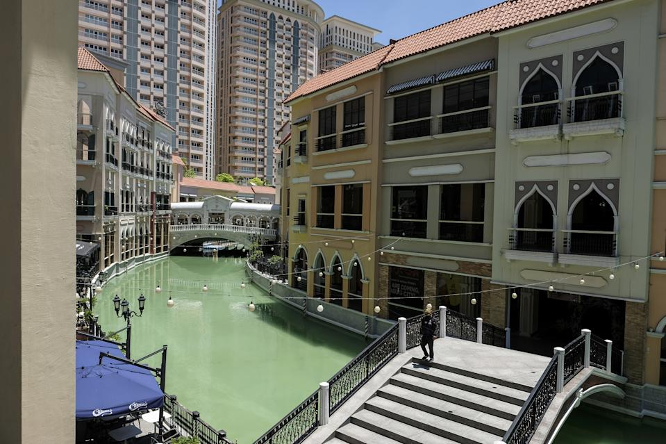A man crosses a bridge over a man-made canal at the Venice Grand Canal Mall operated by Megaworld Corp. in Taguig City, Metro Manila, the Philippines, on Monday, June 22, 2020. The Philippines reimposed a lockdown last week on its central islands' most populous Cebu City where a third of those tested were found infected with the coronavirus, while keeping the loose restrictions in the capital region. Photographer: Veejay Villafranca/Bloomberg