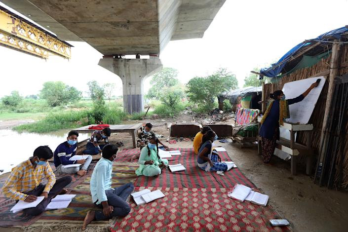 Students in Class 10 who do not have access to the internet and cannot afford electronic devices to attend to online classes study in an open-air class in a slum organized by Satyendra Pal Shakya, a college student, as schools remain closed on July 20 in New Delhi.