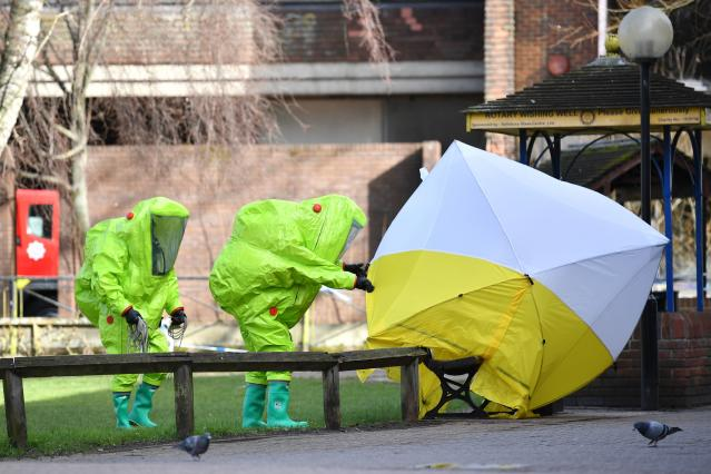 Members of emergency services in green biohazard encapsulated suits fix a tent over the bench where Sergei Skripal and his daughter were found on March 4 in critical condition in Salisbury, England. (BEN STANSALL via Getty Images)
