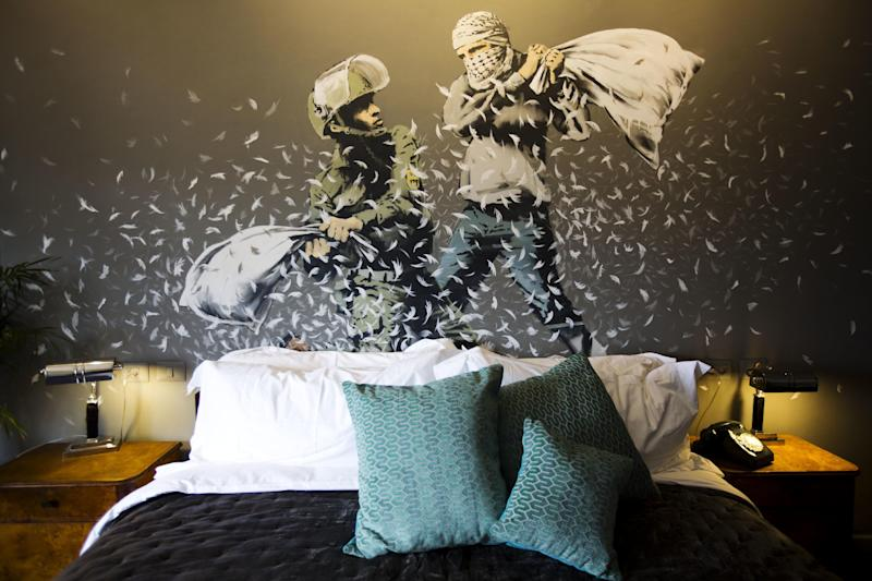 """A Banksy wall painting showing Israeli border policeman and Palestinian in a pillow fight is seen in one of the rooms of the """"The Walled Off Hotel"""" in the West Bank city of Bethlehem, Friday, March 3, 2017. The owner of a guest house packed with the elusive artist Banksy's work has opened the doors of his West Bank establishments to media, showcasing its unique """"worst view in the world."""" The nine-room hotel named """"The Walled Off Hotel"""" will officially open on March 11. (AP Photo/Dusan Vranic)"""