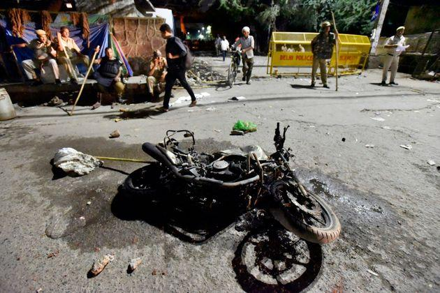 A view of the motorcycle of a Delhi police personnel that was burnt by people during the protest.
