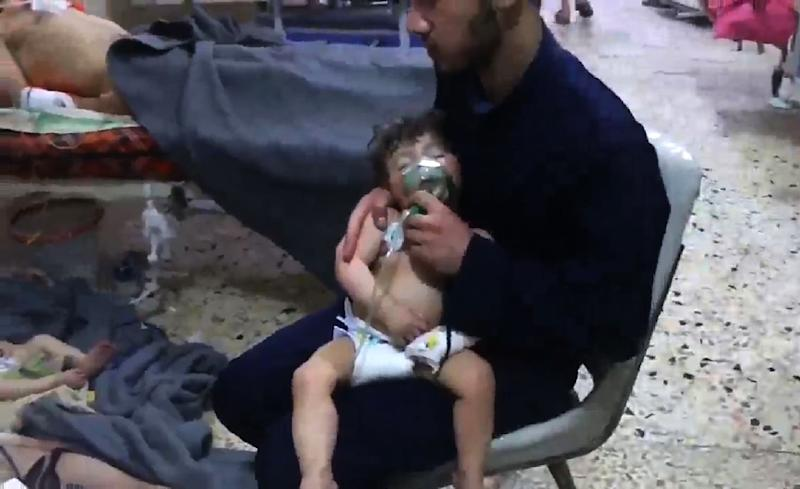 An image grab taken from a video released by the Syrian civil defence in Douma shows unidentified volunteers giving aid to children at a hospital following an alleged chemical attack on the rebel-held town on April 8, 2018 (AFP Photo/HO)