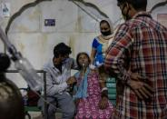 A woman with a breathing problem receives oxygen support for free at a Gurudwara, in Ghaziabad