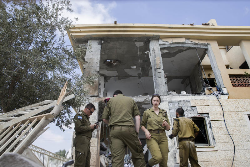 Israeli soldiers stand in front of a house that was hit by a missile fired from Gaza Strip, in the city of Beersheba, southern Israel, Wednesday, Oct. 17, 2018. A medical service said a woman and her three children, whose home was struck, were being treated for shock after they fled to their shelter upon being awoken by warning sirens. (AP Photo/Tsafrir Abayov)