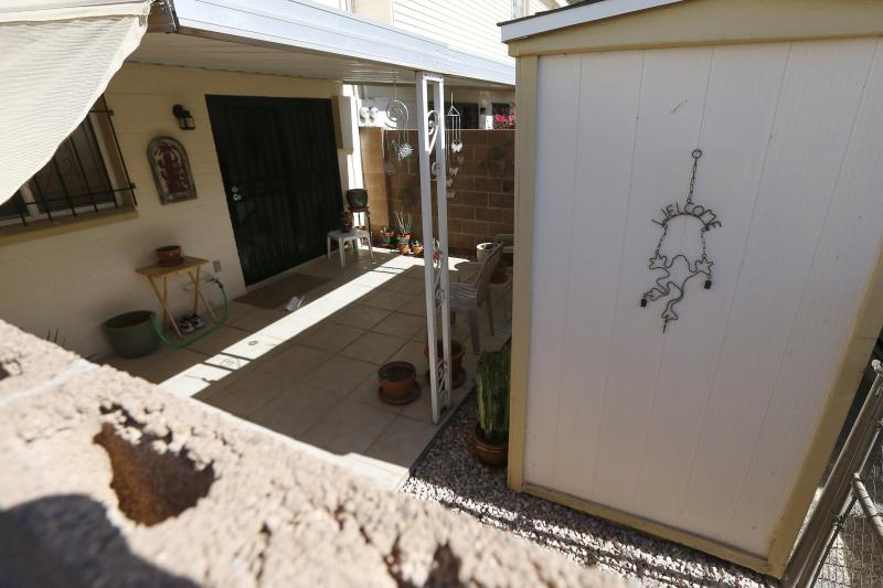 From his own backyard and home in the background, it is believed that this is where Michael Guzzo began his shooting rampage with a shotgun over a shared wall and into the backyard of the Moore home on Monday Oct. 28, 2013, in Phoenix. Police say loud barking dogs might have led to 56-year-old Michael Guzzo to kill four of his neighbors and the neighbors' two dogs before turning the gun on himself, and dying. The victims were identified as Bruce Moore, 66; his daughter, Renee Moore, 36; her husband, Michael Moore, 42, who took his wife's name; and Renee's son, Shannon Moore, 17. (AP Photo/Ross D. Franklin)