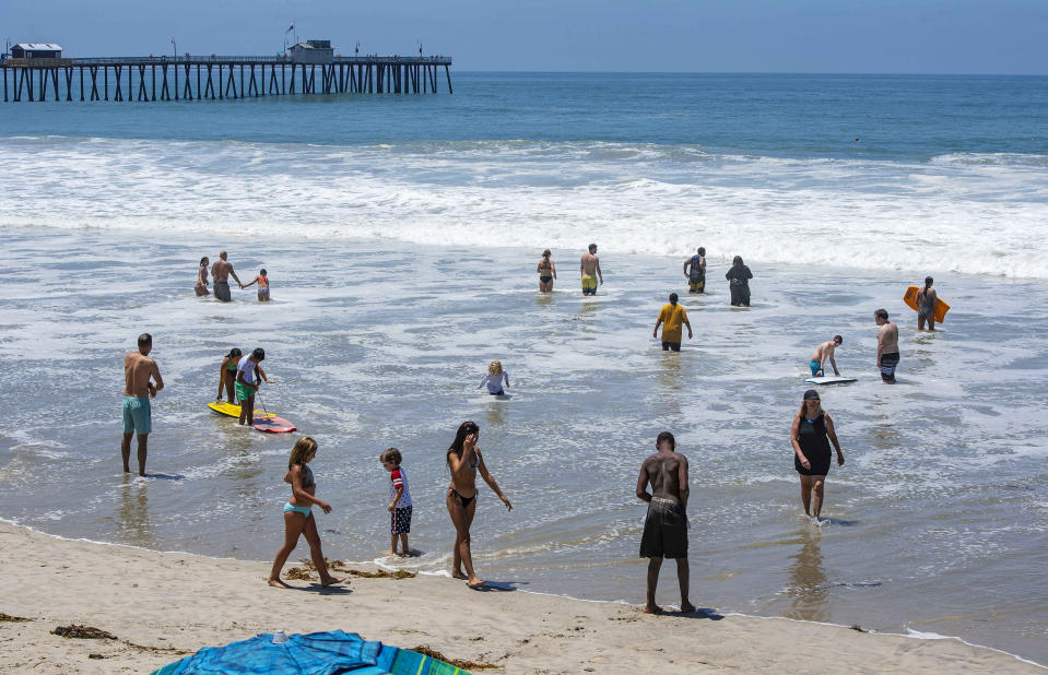 Un reducido número de bañistas disfrutan el mar al norte del muelle San Clemente en San Clemente, California, el sábado 4 de julio de 2020. (Mark Rightmire/The Orange County Register vía AP)