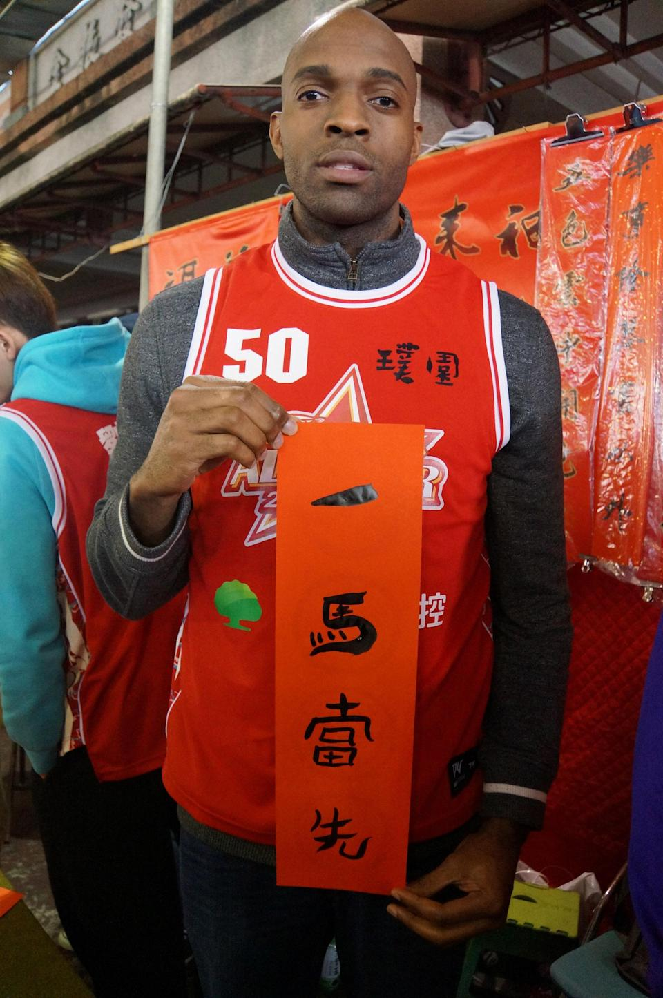 """In this Jan. 17, 2014 photo provided by the Pure Youth Construction basketball team, Quincy Davis III holds a Chinese New Year (Year of the Horse) greeting that reads """"Being The Lead Horse"""" in New Taipei City, Taiwan. When the Pure Youth Construction team's owner suggested in 2013 that Davis join Taiwan's national team, he says he found little motivation to keep his U.S. citizenship. """"When you think about who I am as a black guy in the U.S., I didn't have opportunities,"""" he says. """"You get discriminated against over there in the South. Here everyone is so nice. They invite you into their homes, they're so hospitable. ... There's no crime, no guns. I can't help but love this place."""" (AP Photo/Pure Youth Construction basketball team)"""
