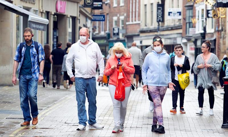 A family in face masks walk along Coney Street, one of the main shopping streets in York.