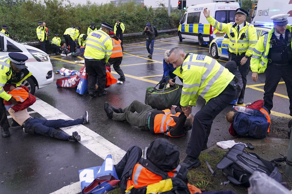 Police officers detain a protester from Insulate Britain occupying a roundabout leading from the M25 motorway to Heathrow Airport in London. Picture date: Monday September 27, 2021. (Photo by Steve Parsons/PA Images via Getty Images)