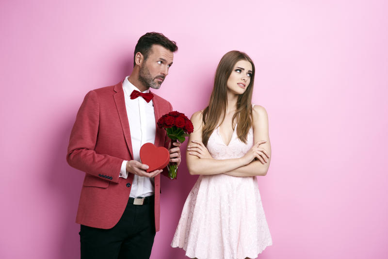 Man with bunch of rose and chocolate box apologizing fiance