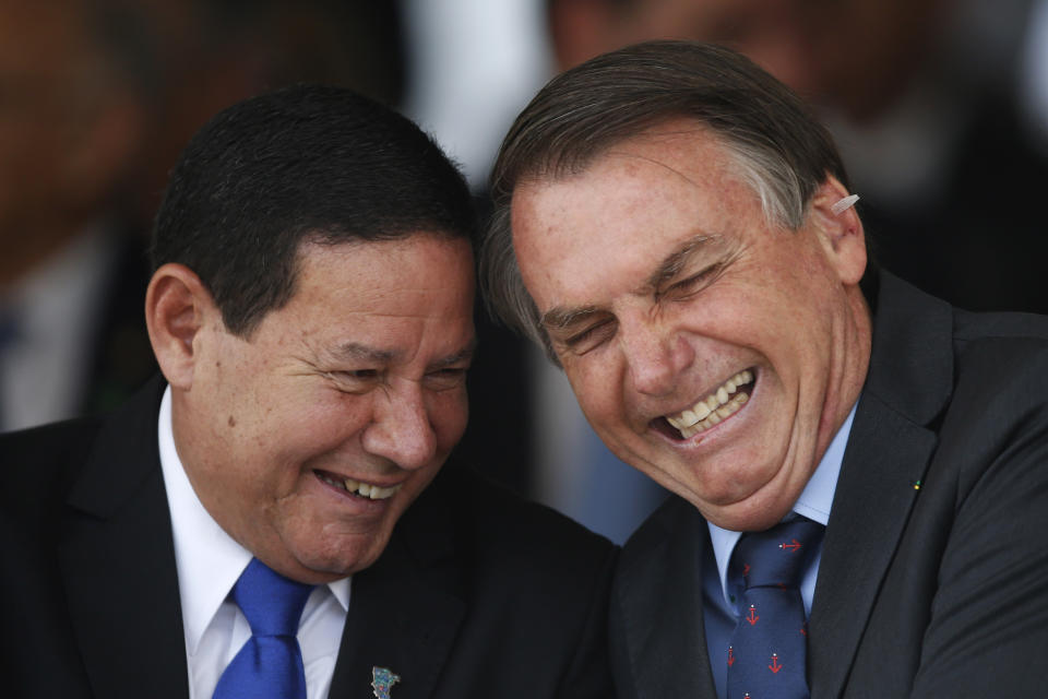 Brazil's President Jair Bolsonaro, right, has a laugh with Vice President Hamilton Mourao, during a military ceremony in honor of Sailor Day, in Brasilia, Brazil, Friday, Dec. 13, 2019. (AP Photo/Eraldo Peres)
