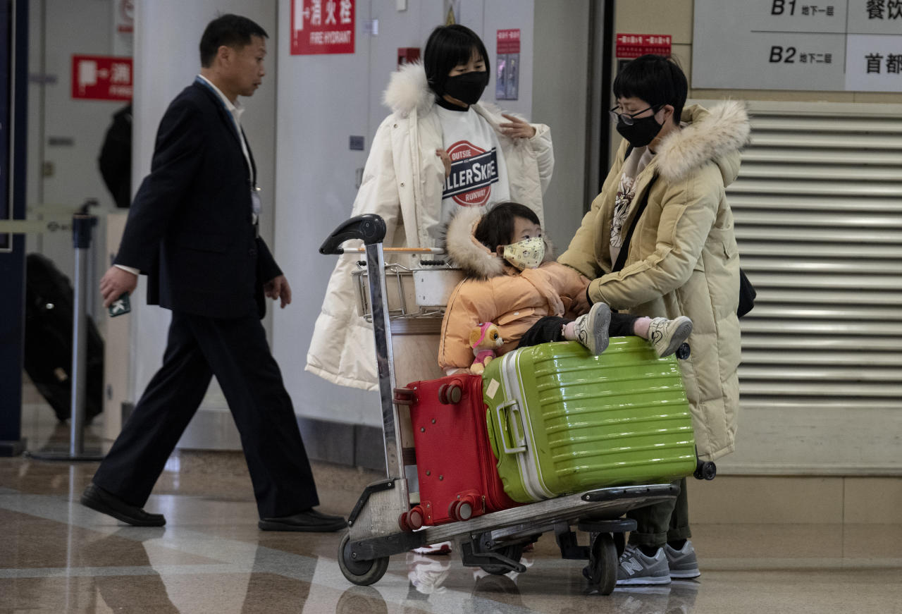 Travellers wearing protective masks arrivin at the Beijing Capital Airport in Beijing
