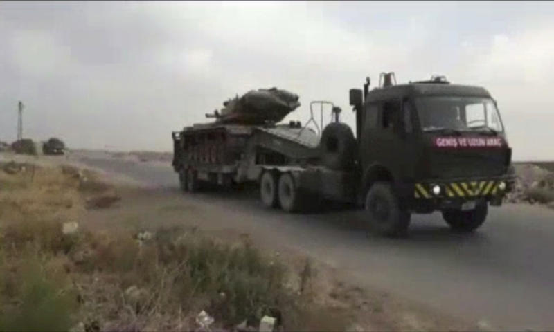 This frame grab from video provided by Central Station for Turkish Intervention, an activist-operated media group monitoring Turkish activities in Syria, that is consistent with independent AP reporting, shows a Turkish military truck carrying a tank heading to some of the 12 Turkish observations points that ring Idlib, Syria, Thursday, Sept. 13, 2018. Turkey sent in military reinforcements Thursday to beef up its positions inside Syria's last rebel bastion Idlib, activists reported, even as the Turkish defense minister said Ankara is still trying with Russia and Iran to prevent a humanitarian tragedy in the case of a threatened Syrian government offensive. (Central Station for Turkish Intervention, via AP)