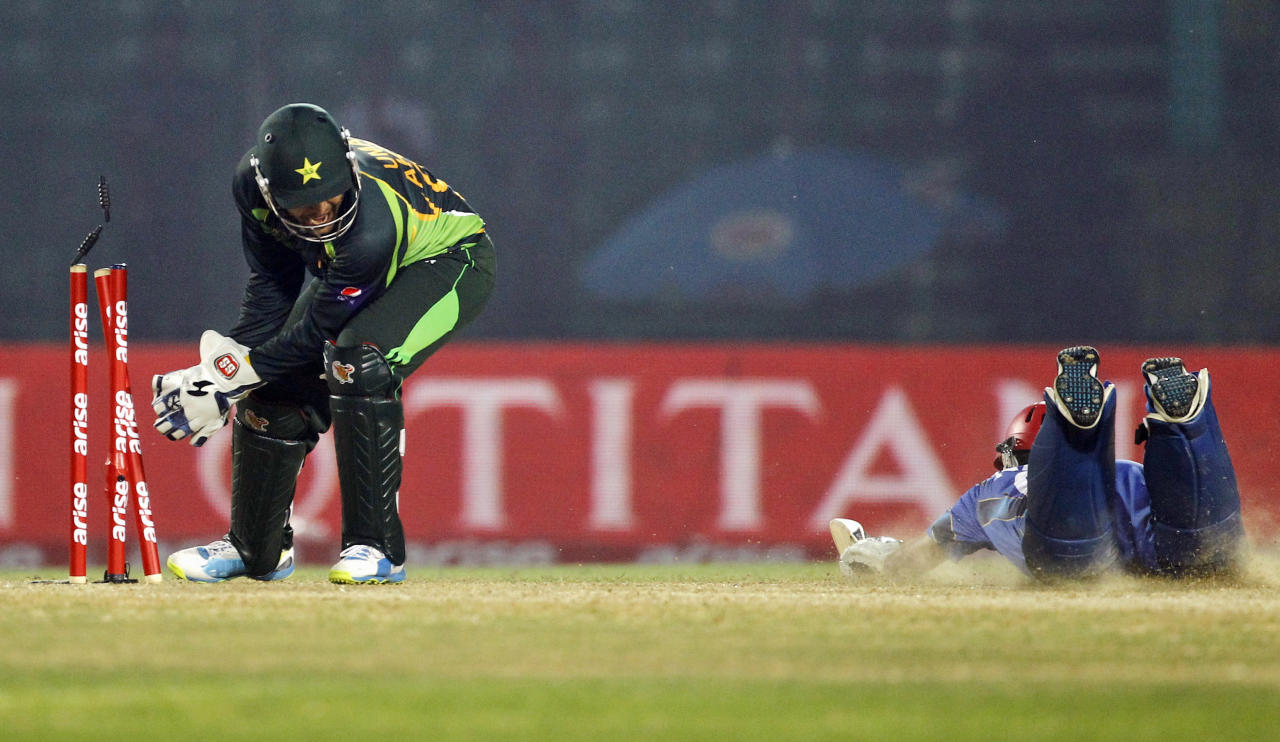 Pakistan's wicketkeeper Umar Akmal, left, unsuccessfully dislodges the bails during the Asia Cup one-day international cricket tournament against Afghanistan in Fatullah, near Dhaka, Bangladesh, Thursday, Feb. 27, 2014. Pakistan won by 72 runs. (AP Photo/A.M. Ahad)